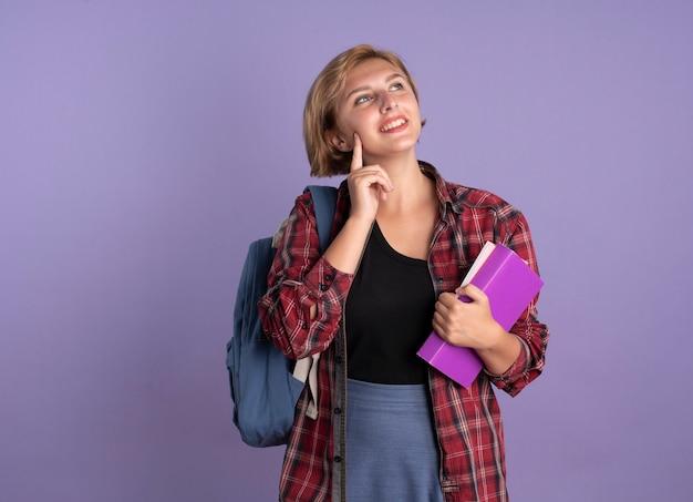 Glimlachend jong slavisch studentenmeisje met rugzak legt vinger op gezicht houdt boek en notitieboekje omhoog kijkend