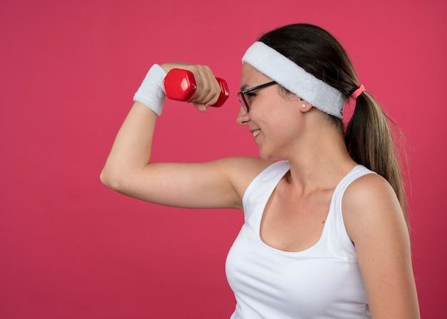 Glimlachend jong sportief meisje in optische bril met hoofdband en polsbandjes houdt halters en kijkt naar dumbbell