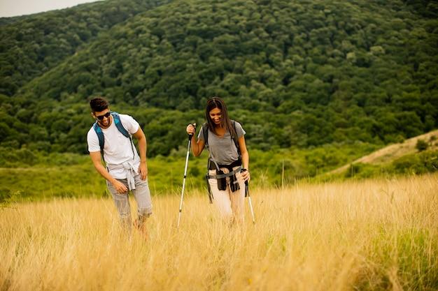 Glimlachend jong stel dat met rugzakken over groene heuvels loopt