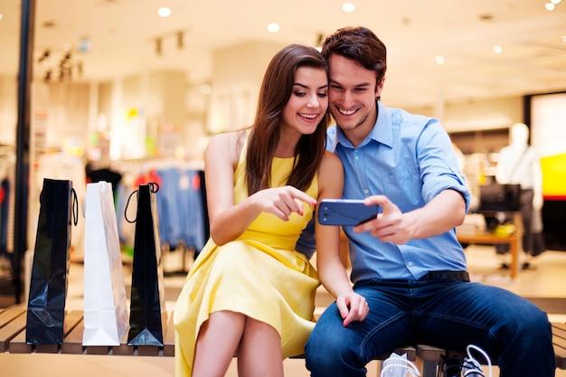 Glimlachend jong stel dat mobiele telefoon bekijkt