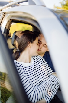 Glimlachend jong stel in een auto. kussen in de auto