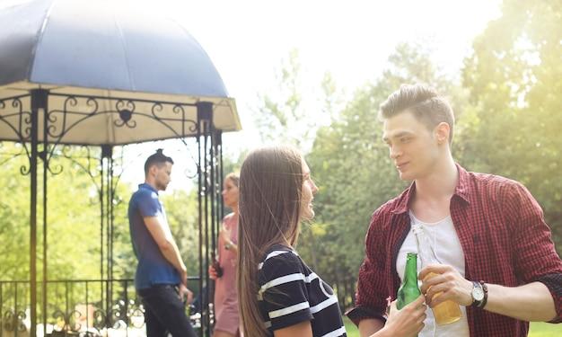 Glimlachend jong stel met bier en kijken naar elkaar terwijl twee mensen barbecueën op de achtergrond.