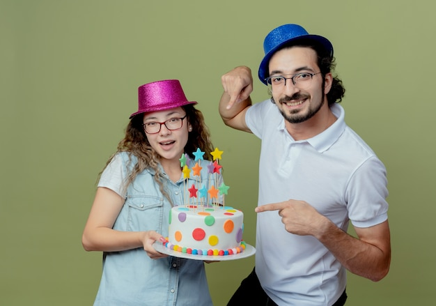 Glimlachend jong stel met roze en blauwe hoed man wijst naar verjaardagstaart in haar hand geïsoleerd op olijfgroen