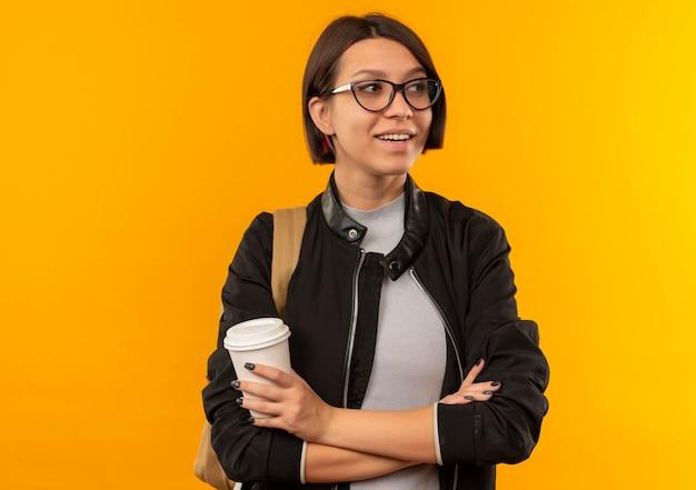 Glimlachend jong studentenmeisje die glazen en achterzak dragen die zich met gesloten houding bevinden die plastic koffiekop houden die kant bekijken die op oranje muur wordt geïsoleerd