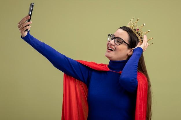Glimlachend jong superheld meisje met bril en kroon hand zetten kroon en neem selfie geïsoleerd op olijfgroene achtergrond