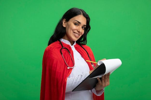 Glimlachend jong superheldenmeisje dat recht vooruit kijkt terwijl het dragen van medische mantel met een stethoscoop houdt en iets schrijft op klembord dat op groen wordt geïsoleerd