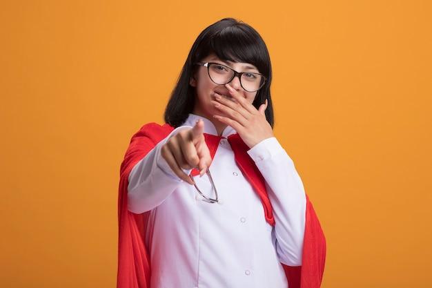 Glimlachend jong superheldenmeisje die stethoscoop met medisch kleed en mantel met glazen dragen die u gebaar en behandelde mond met hand tonen