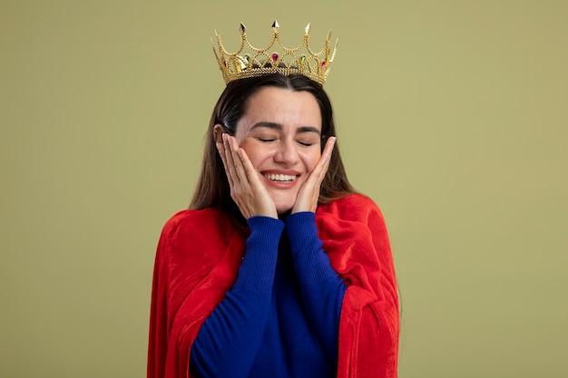 Glimlachend jong superheldmeisje met gesloten ogen die kroon dragen die handen op wangen zetten die op olijfgroene achtergrond worden geïsoleerd