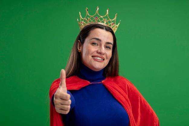 Glimlachend jong superheromeisje die kroon dragen die duim tonen die omhoog op groene achtergrond wordt geïsoleerd