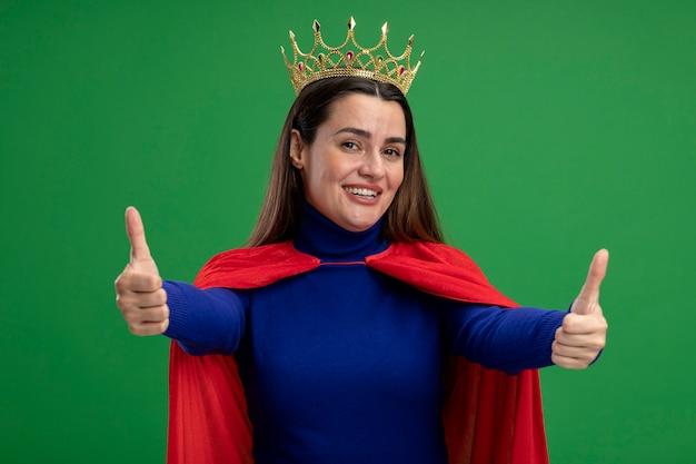 Glimlachend jong superheromeisje die kroon dragen die duimen tonen die omhoog op groen worden geïsoleerd