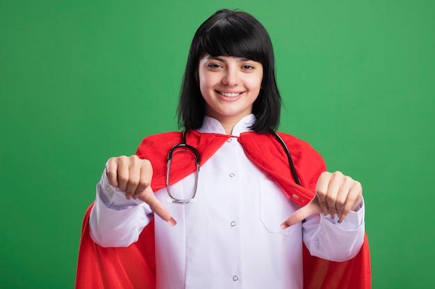 Glimlachend jong superheromeisje die stethoscoop met medisch gewaad en mantel dragen die duimen tonen die neer op groene muur worden geïsoleerd