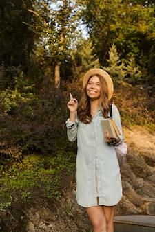 Glimlachend jong tienermeisje met rugzak het lopen