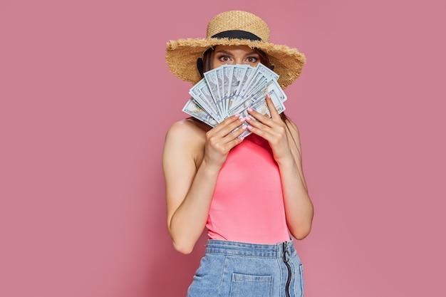 Glimlachend jong toeristenmeisje in strohoed houdt fan van contant geld in dollarbankbiljetten