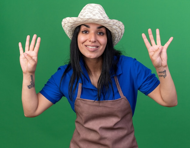 Glimlachend jong tuinmanmeisje dat uniform en hoed draagt en naar de voorkant kijkt met acht met handen geïsoleerd op groene muur