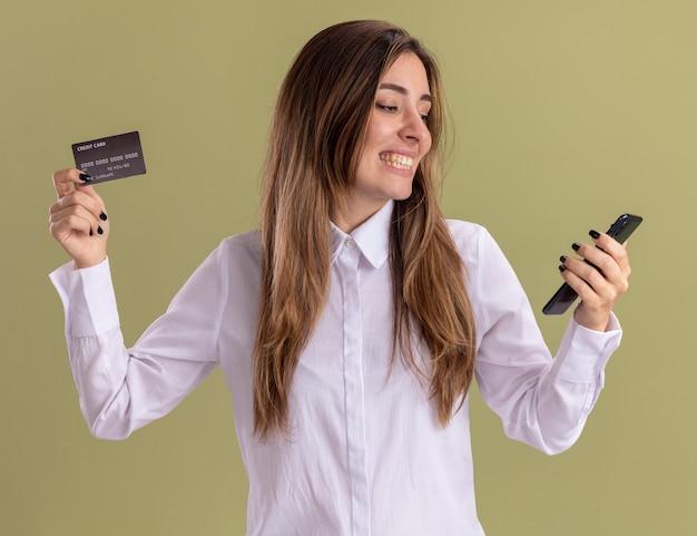Glimlachend jong, vrij blank meisje houdt creditcard vast en kijkt naar telefoon geïsoleerd op olijfgroene muur met kopieerruimte