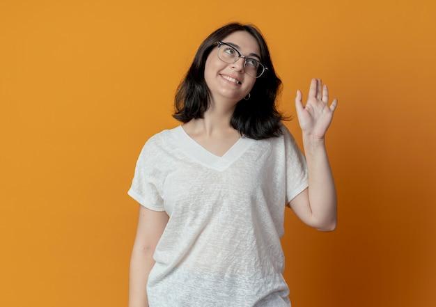 Glimlachend jong vrij kaukasisch meisje dat een bril draagt die omhoog kijkt en hallo gesturing op oranje achtergrond met exemplaarruimte wordt geïsoleerd