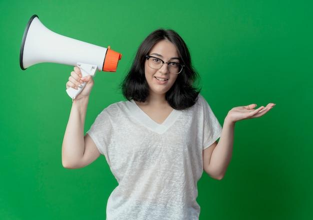 Glimlachend jong vrij kaukasisch meisje dat glazen draagt die spreker houdt en lege die hand toont die op groene achtergrond wordt geïsoleerd