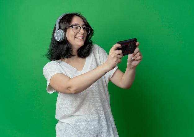 Glimlachend jong vrij kaukasisch meisje die glazen en hoofdtelefoons dragen die en mobiele telefoon houden bekijken die op groene achtergrond met exemplaarruimte wordt geïsoleerd