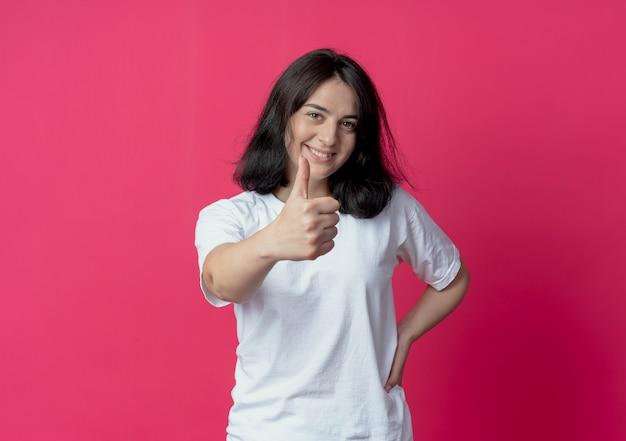 Glimlachend jong vrij kaukasisch meisje die hand op taille zetten en duim tonen die omhoog op karmozijnrode achtergrond met exemplaarruimte wordt geïsoleerd