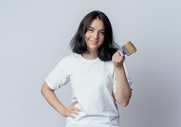 Glimlachend jong vrij kaukasisch meisje die hand op taille zetten en verfborstel houden die op witte achtergrond met exemplaarruimte wordt geïsoleerd