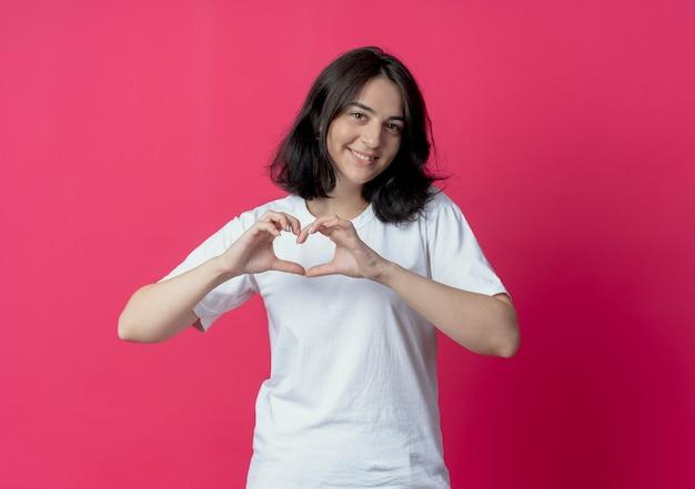 Glimlachend jong vrij kaukasisch meisje die hartteken doen bij camera die op karmozijnrode achtergrond met exemplaarruimte wordt geïsoleerd
