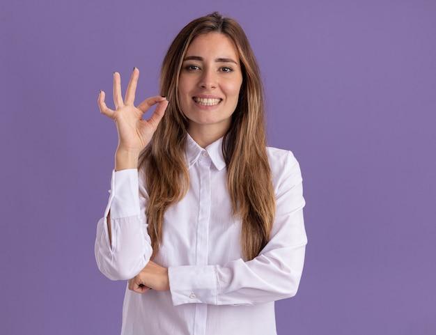 Glimlachend jong, vrij kaukasisch meisje gebaren ok handteken geïsoleerd op paarse muur met kopie ruimte