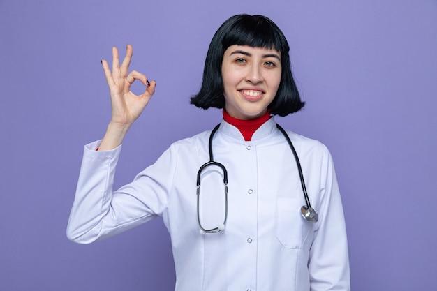 Glimlachend jong, vrij kaukasisch meisje in doktersuniform met een stethoscoop die ok teken gebaart