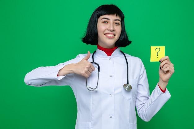 Glimlachend jong, vrij kaukasisch meisje in doktersuniform met een stethoscoop die omhoog duimt en vraagnota vasthoudt