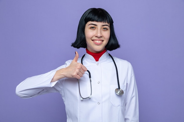 Glimlachend jong vrij kaukasisch meisje in doktersuniform met stethoscoop duimen omhoog