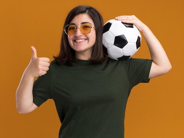 Glimlachend jong, vrij kaukasisch meisje in zonnebril duimen omhoog en houdt bal op schouder geïsoleerd op oranje muur met kopieerruimte