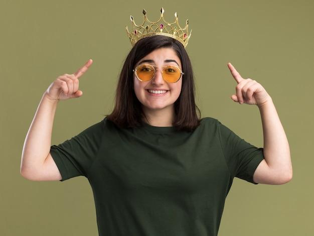 Glimlachend jong vrij kaukasisch meisje in zonnebril met kroon die met twee handen benadrukt die op olijfgroene muur met exemplaarruimte wordt geïsoleerd