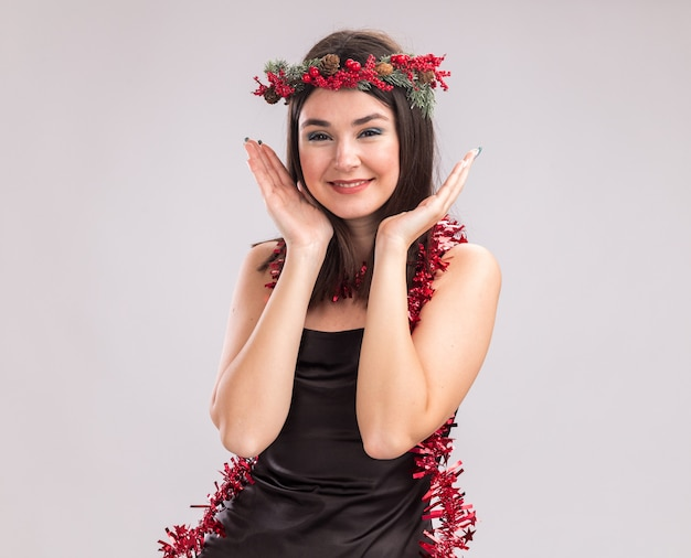 Glimlachend jong vrij kaukasisch meisje met kerst hoofd krans en klatergoud slinger om nek kijken camera houden handen in de buurt van hoofd geïsoleerd op een witte achtergrond met kopie ruimte
