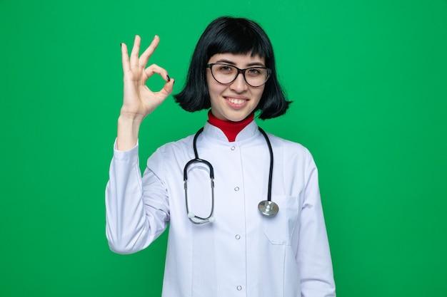 Glimlachend jong, vrij kaukasisch meisje met optische bril in doktersuniform met stethoscoop, gebarend ok teken