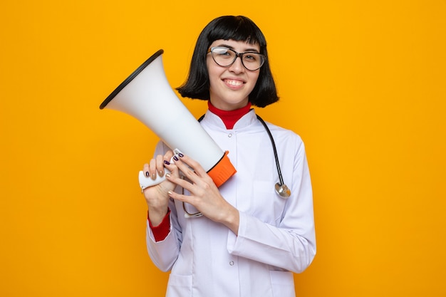 Glimlachend jong, vrij kaukasisch meisje met optische bril in doktersuniform met stethoscoop met luidspreker