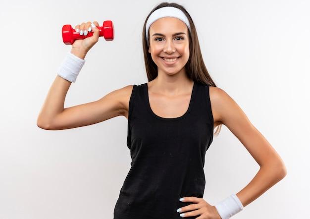 Glimlachend jong vrij sportief meisje die hoofdband en polsbandje dragen die domoor houden die hand op taille zetten die op witte ruimte wordt geïsoleerd
