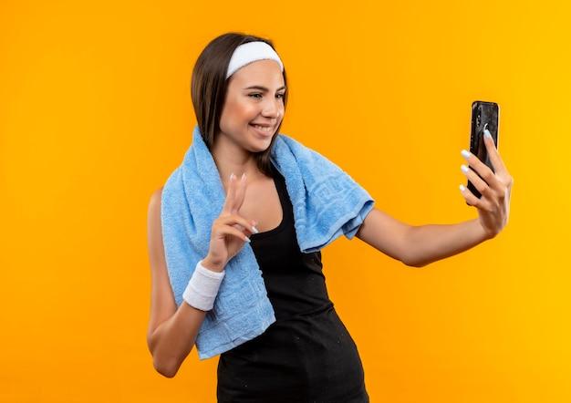 Glimlachend jong vrij sportief meisje die hoofdband en polsbandje dragen die en mobiele telefoon met handdoek om haar hals houden bekijken die op oranje ruimte wordt geïsoleerd