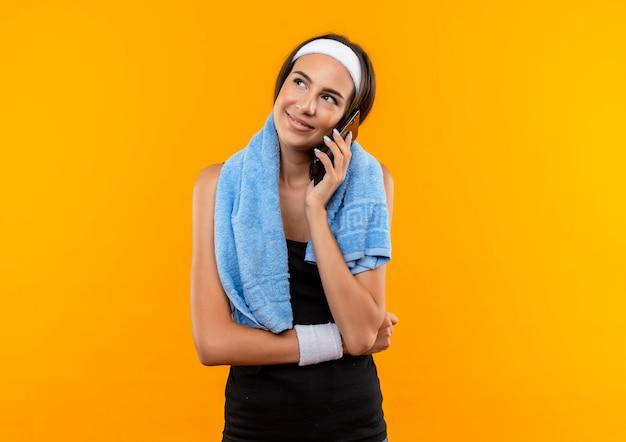 Glimlachend jong vrij sportief meisje die hoofdband en polsbandje dragen die op telefoon met handdoek om haar hals op oranje ruimte spreken