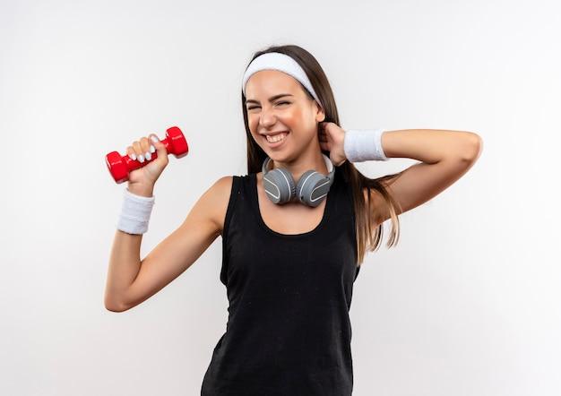 Glimlachend jong vrij sportief meisje die hoofdband en polsbandje en hoofdtelefoons op hals dragen die domoor opheffen die hand op hals zetten die op witte ruimte wordt geïsoleerd