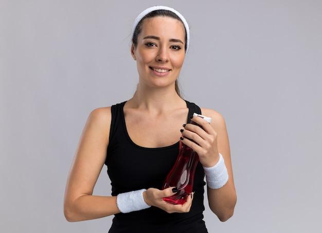 Glimlachend jong, vrij sportief meisje met een hoofdband en polsbandjes met een waterfles