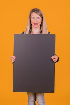Glimlachend jong vrouw die leeg zwart aanplakbiljet houden die camera tegen oranje achtergrond bekijken