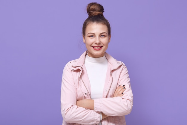 Glimlachend jong vrouwenmeisje in lichtroze jasje en wit overhemd poseren geïsoleerd op lila muur, handen houden gekruist, vrouwelijk, positieve emoties uitdrukken.