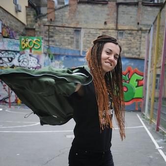 Glimlachend jong vrouwenportret met dreadlocks, tegen graffiti