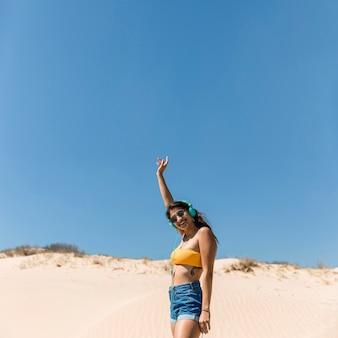 Glimlachend jong wijfje in hoofdtelefoons op strand
