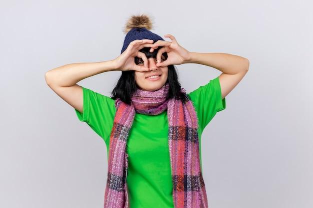 Glimlachend jong ziek kaukasisch meisje dat de winterhoed en sjaal draagt die blikgebaar doet die handen als verrekijker gebruikt die op witte muur met exemplaarruimte wordt geïsoleerd