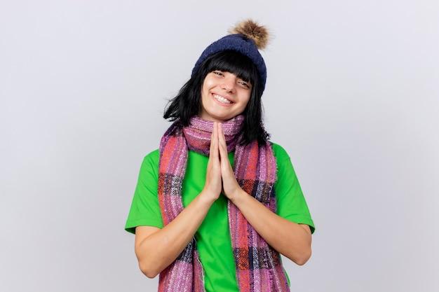 Glimlachend jong ziek kaukasisch meisje die de winterhoed en sjaal dragen die handen samen houden die camera bekijken die op witte achtergrond met exemplaarruimte wordt geïsoleerd