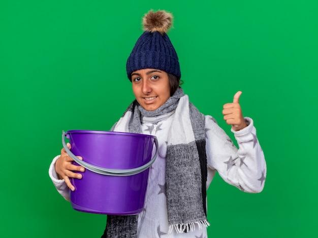 Glimlachend jong ziek meisje dat de winterhoed met sjaal draagt die plastic emmer houdt die duim toont die omhoog op groen wordt geïsoleerd