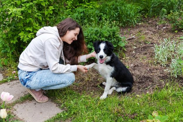 Glimlachend jonge aantrekkelijke vrouw omarmen schattige puppy hondje border collie in zomer stadspark buiten achtergrond. meisje knuffelen nieuw mooi lid van de familie. dierenverzorging en dierenconcept