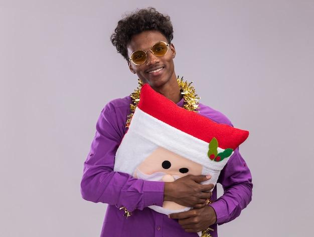Glimlachend jonge afro-amerikaanse man dragen van een bril met klatergoud slinger rond nek houden santa claus kussen kijken camera geïsoleerd op witte achtergrond