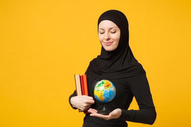Glimlachend jonge arabische moslim student meisje in hijab zwarte kleren houden in handen globe, boeken geïsoleerd op gele muur portret. mensen religieuze levensstijl concept.