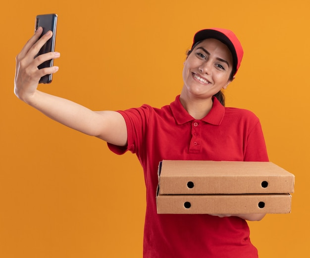 Glimlachend jonge bezorger die uniform en pet draagt die pizzadozen houdt en een selfie neemt die op oranje muur wordt geïsoleerd